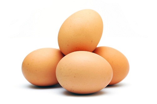 A pile of four brown eggs